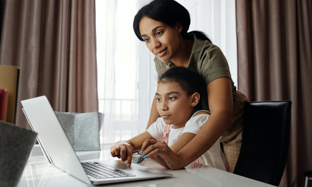 mother and daughter working on a laptop